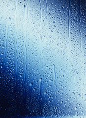 Water drops running down blue Glass