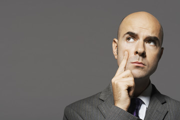 Bald businessman with hand on chin, thinking