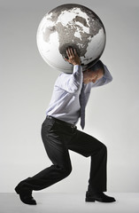 Businessman struggling, carrying globe on shoulders, side view
