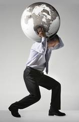 Businessman struggling, carrying globe on shoulders, side view