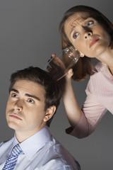 Woman listening through glass to man's head