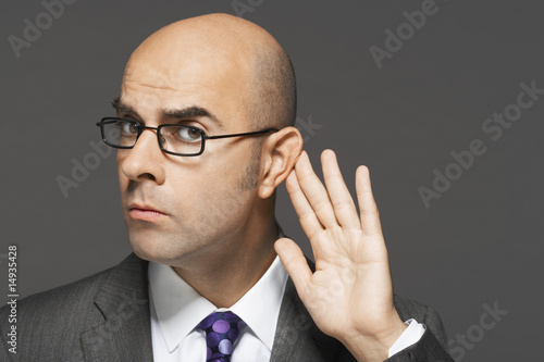 Balding man with hand behind ear, listening closely