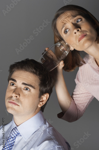 Woman listening through glass to man's head