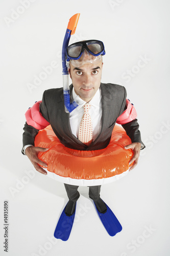 Middle-aged businessman in flippers, inflatable rubber ring, snorkel and goggles