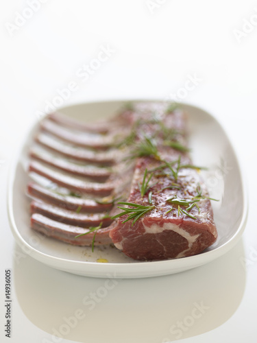 Plate of Fresh, raw Ribs with rosemary sprinkled on it