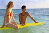 hawaiian beach boy teaches surfing to a blond tourist poster