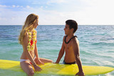 hawaiian beach boy teaches surfing to a blond tourist