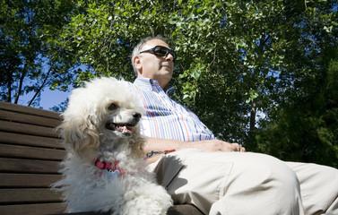 uomo con il suo cane seduto al parco