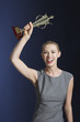 Woman hoisting trophy over head against dark background