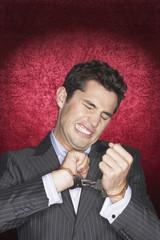 Man straining in handcuffs against red velvet background