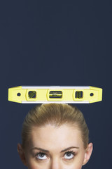 Woman balancing spirit level on her head against dark background, high section