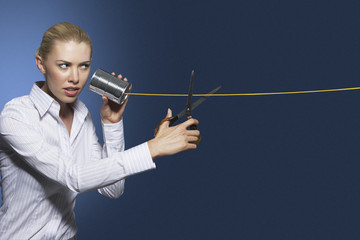 Woman cutting line on tin can string phone, against dark background