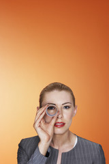 Woman looking through paper tube against orange background