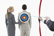 Business woman holding target to man's back while other man close-up of hands aims bow and arrow, against white background