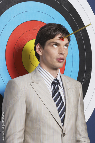 Man with toy arrow on forehead, standing in front of target