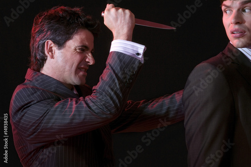 Man stabbing another man in back against black background