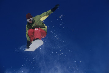 Snowboarder jumping, holding snowboard