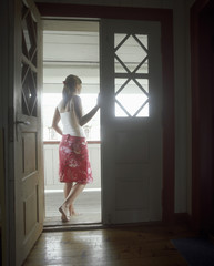 Woman standing in open door,  Looking Out, back view