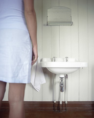 Woman Standing in Bathroom, mid section, back view