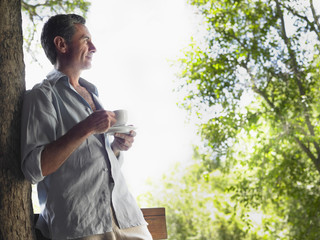 Mature man drinking tea, leaning on tree, looking at view, profile