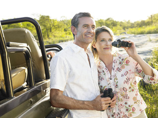 Couple standing by jeep holding binoculars, smiling