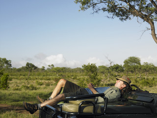 Adult man lying on bonnet of jeep, having nap