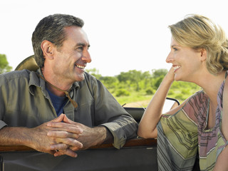 Man and woman talking, woman leaning elbow on door of jeep, smiling