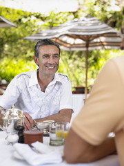 Two men having conversation at table, selective focus