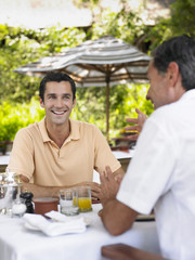 Two men having conversation at table, laughing, selective focus
