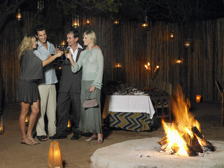 Four people toasting at outdoor nightclub near bonfire, night
