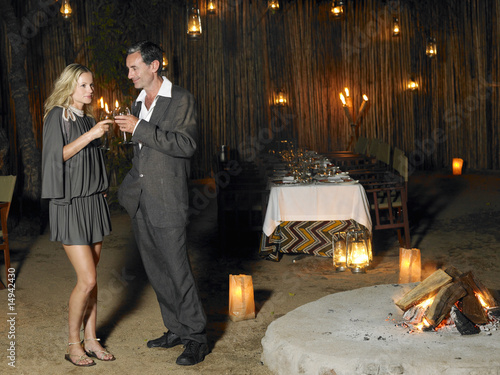Man and woman toasting at outdoor nightclub near bonfire, night