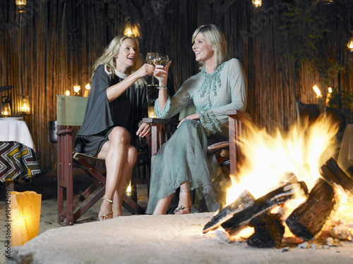 Two women sitting by bonfire at outdoor nightclub, toasting