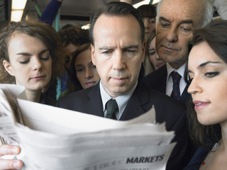 Commuters standing on train, reading newspaper over shoulder