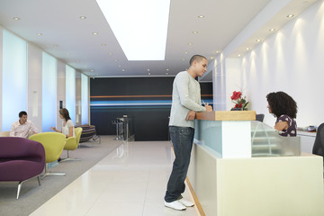 Man standing at reception desk, Talking to Receptionist, side view