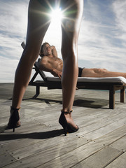 Man reclining on deck chair looking up at woman on deck