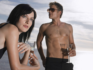 Man and woman drinking champagne near ocean