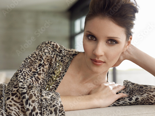 Young woman leaning on elbow indoors, close-up, portrait