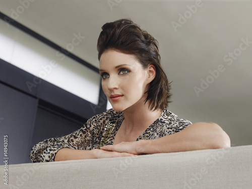 Young woman leaning on couch indoors