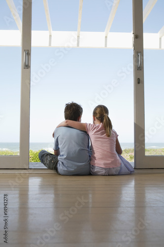 Young girl and boy sitting on floor in doorway, back view