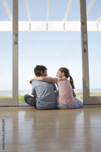 Young girl with arm around young boy sitting on floor in doorway