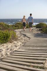 Boy and girl walking hand in hand, along boardwalk toward sea, back view