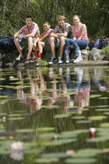 Group portrait of teenage girls and boys 16-17 years sitting by lake, smiling
