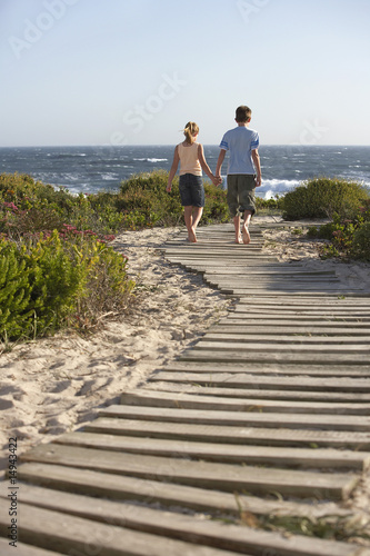 Boy and girl walking hand in hand, along boardwalk toward sea, back view