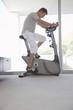Mature man on exercise bike, pedalling, side view