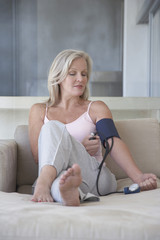 Mature woman sitting on sofa, barefoot checking blood pressure with sphygmometer