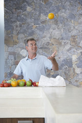 Mature man throwing orange into air, standing at kitchen countertop