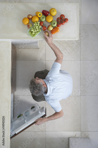 Mature man squatting, putting fruit in refrigerator, view from above
