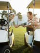 Young golfers sitting in golf cart, holding score card
