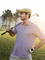 Young male golfer standing on course, holding club on shoulder