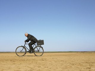 Businessman riding bicycle in desert